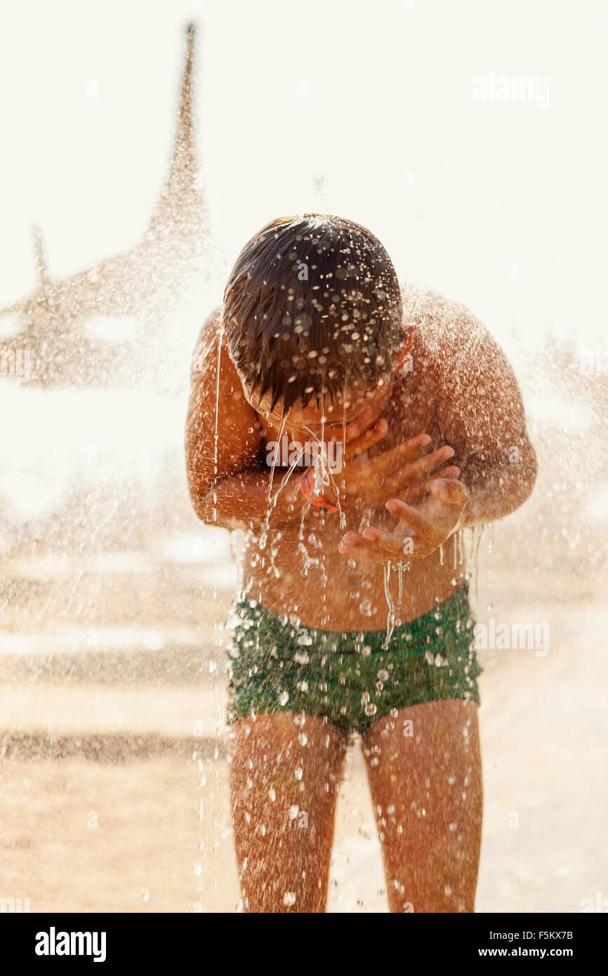 La Turchia, Alanya, ragazzo (10-11) sotto la doccia sulla spiaggia Immagini Stock
