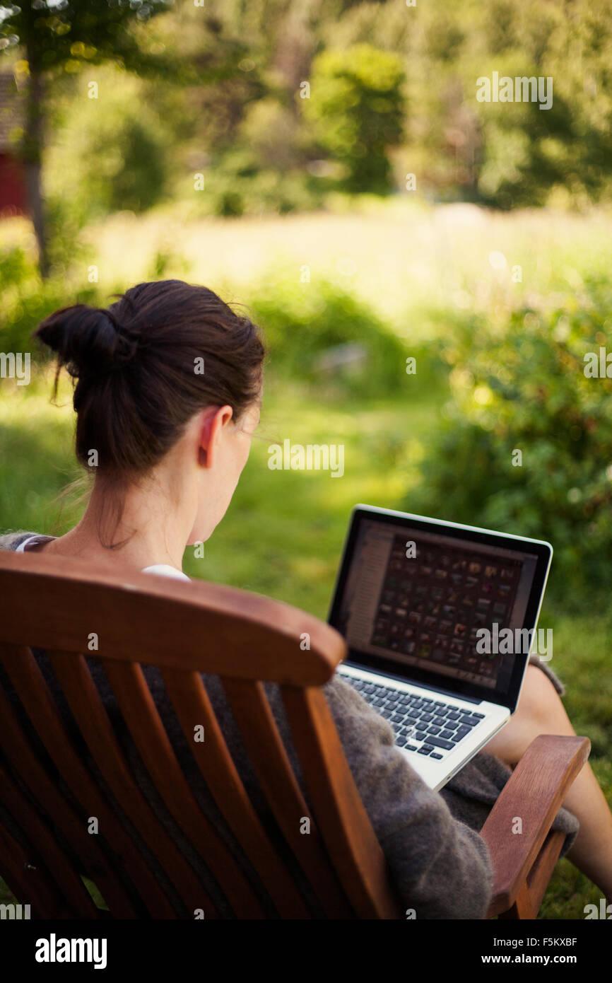 La Svezia, Halsingland, Jarvso, Donna utilizzando laptop in giardino Immagini Stock