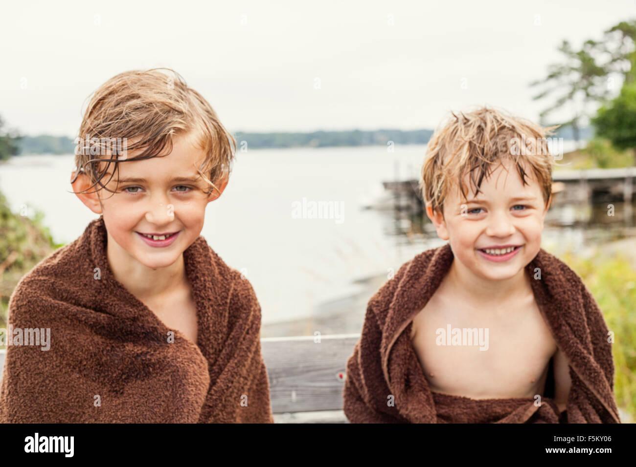 La Svezia, Uppland, Runmaro, Barrskar, ritratto di due ragazzi avvolti in asciugamani Immagini Stock