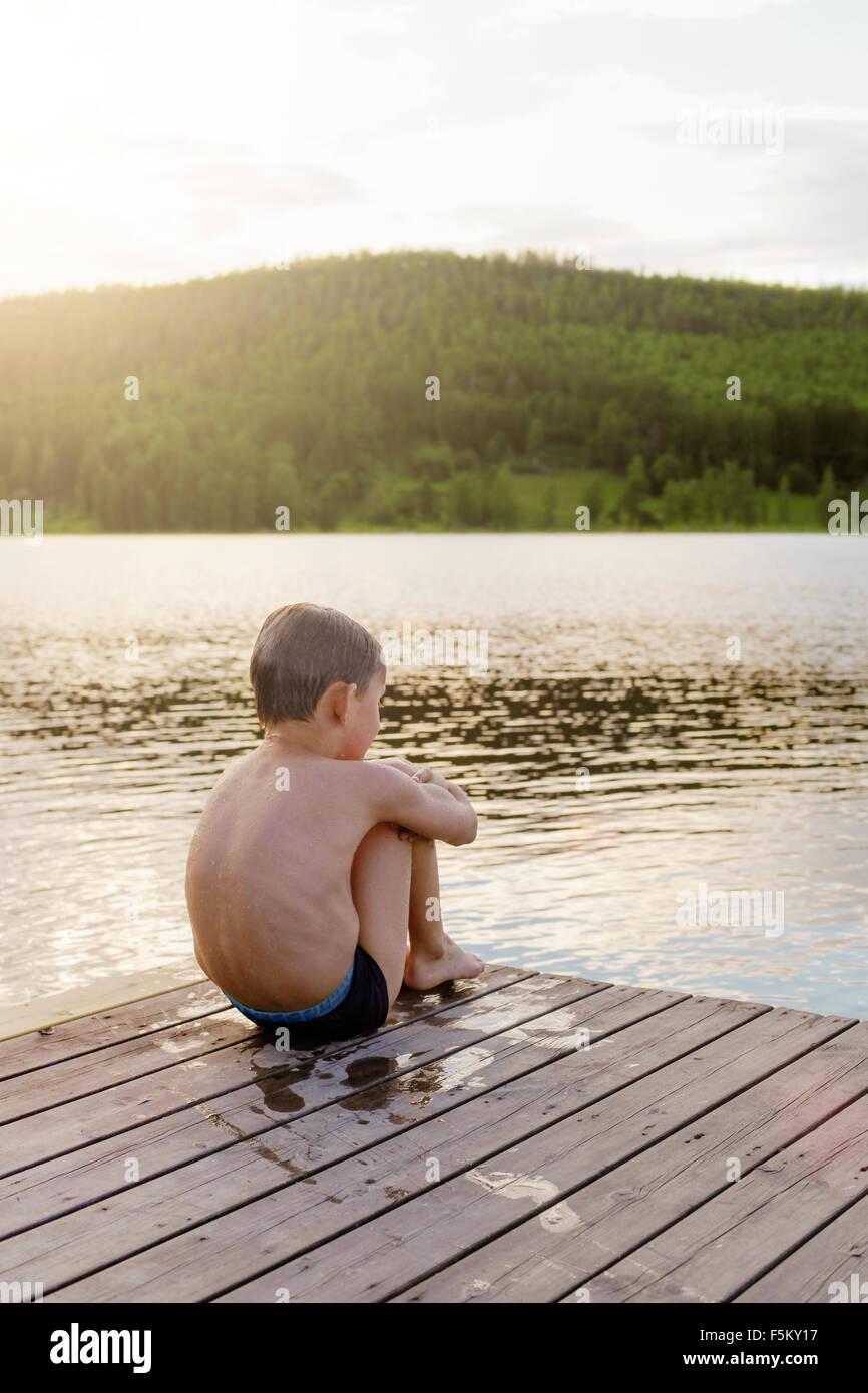 La Svezia, Halsingland, Jarvso, ragazzo (6-7) seduto sul lago di garda Immagini Stock