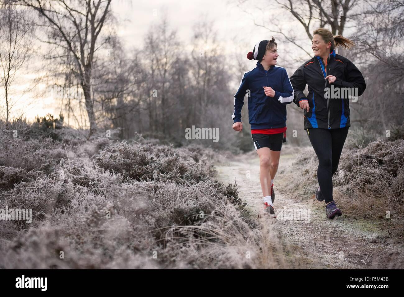 Vista frontale della madre e del figlio in esecuzione su frosty il percorso faccia a faccia sorridente Immagini Stock