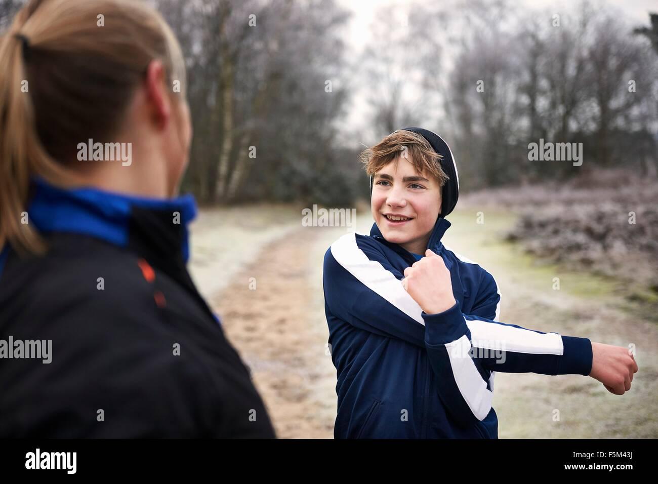 Ragazzo adolescente stretching braccio, guardando la madre sorridente Immagini Stock