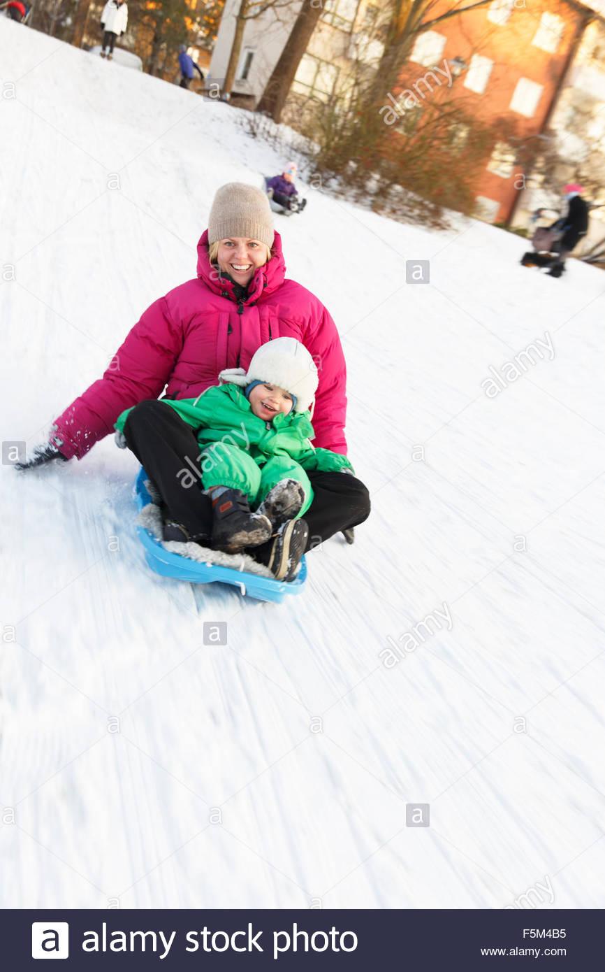 La Svezia Sodermanland, Stoccolma, Arsta, madre e figlio (2-3) discesa in slittino snowy hill Immagini Stock