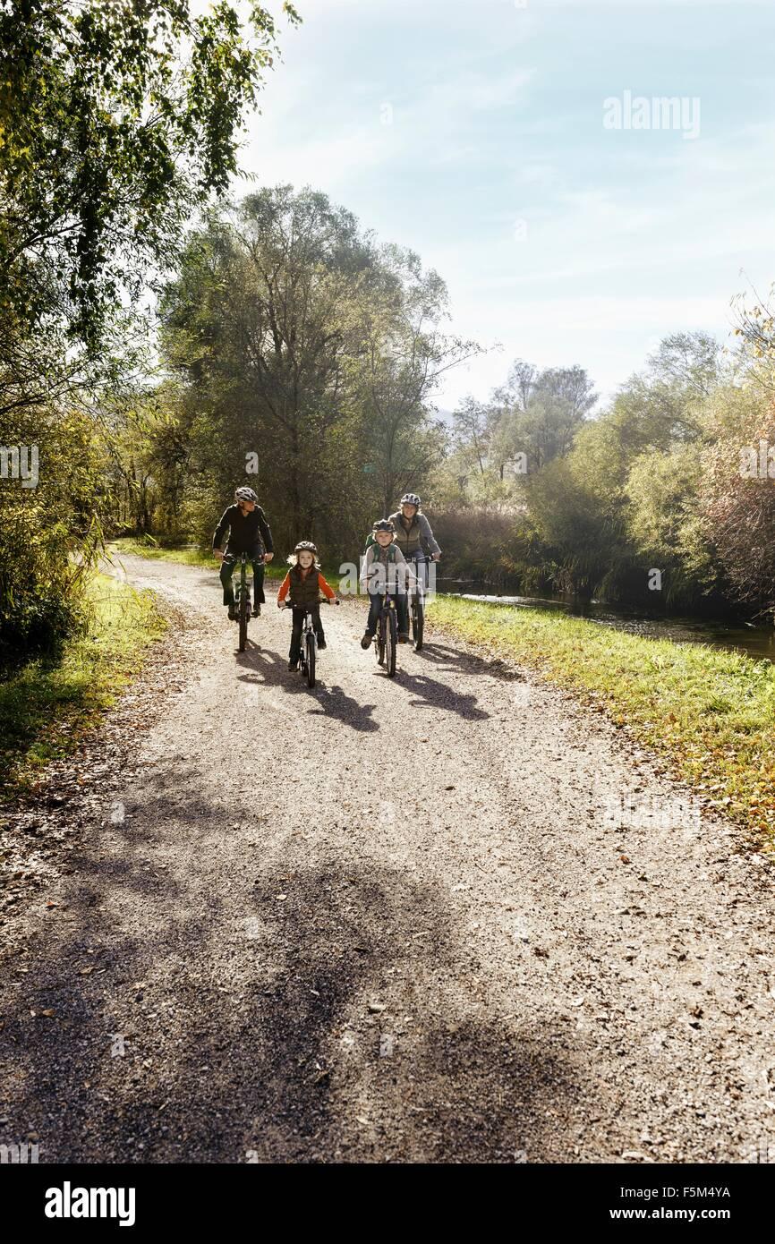 Vista frontale della famiglia sulla strada rurale equitazione biciclette Immagini Stock