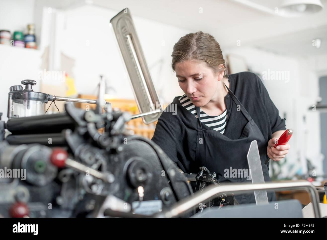 Stampante femmina prepara stampa la macchina in officina Immagini Stock