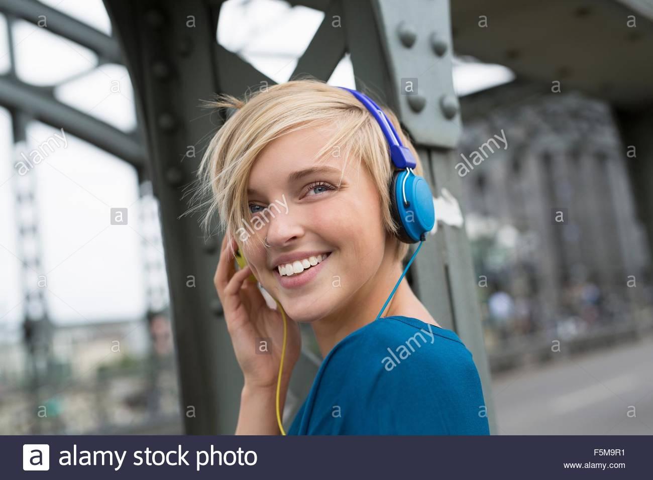 Felice giovane donna che indossa le cuffie sul ponte guardando sopra la sua spalla Immagini Stock