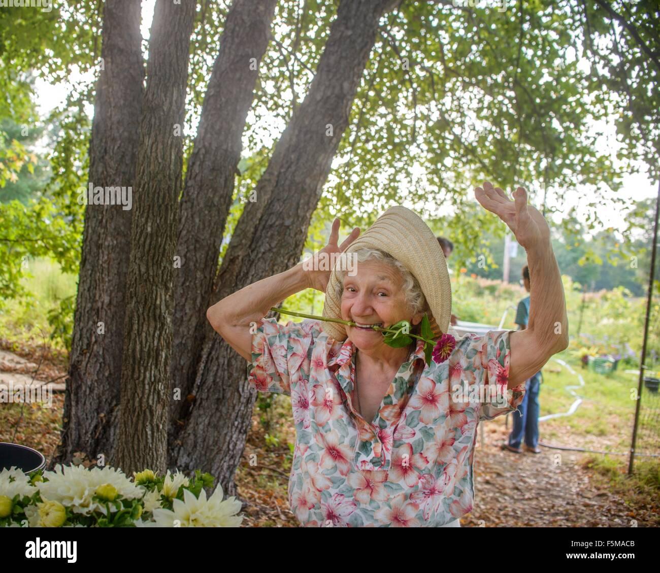 Senior donna con fiore in bocca dancing in agriturismo Immagini Stock
