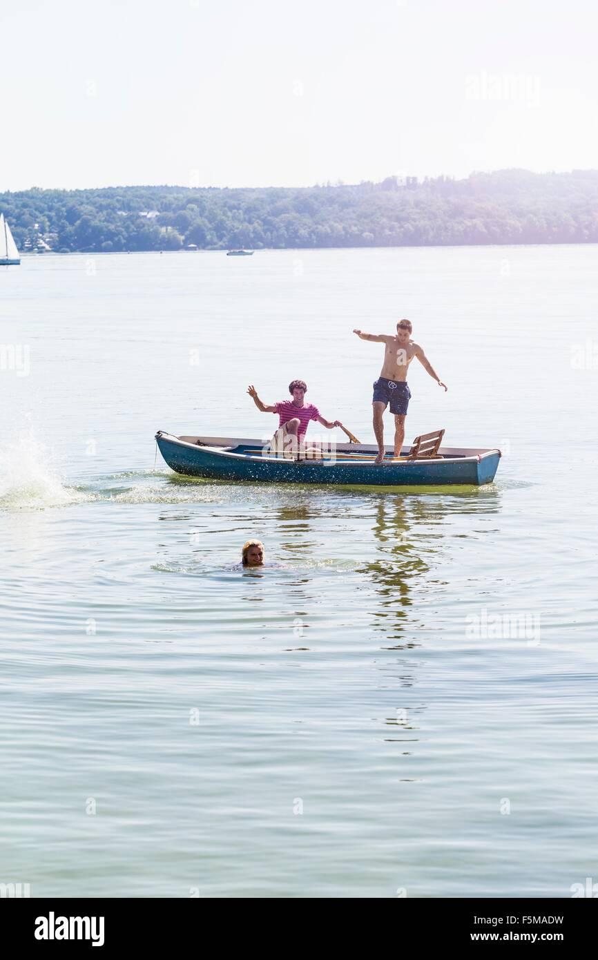Gli amici di saltare fuori in barca e nuotare nel lago, Schondorf, Ammersee, Baviera, Germania Immagini Stock