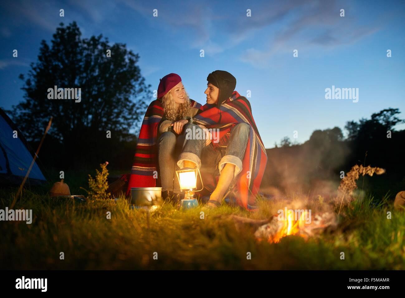 Campeggio giovani giovane seduto di fronte ad un falò al tramonto Immagini Stock