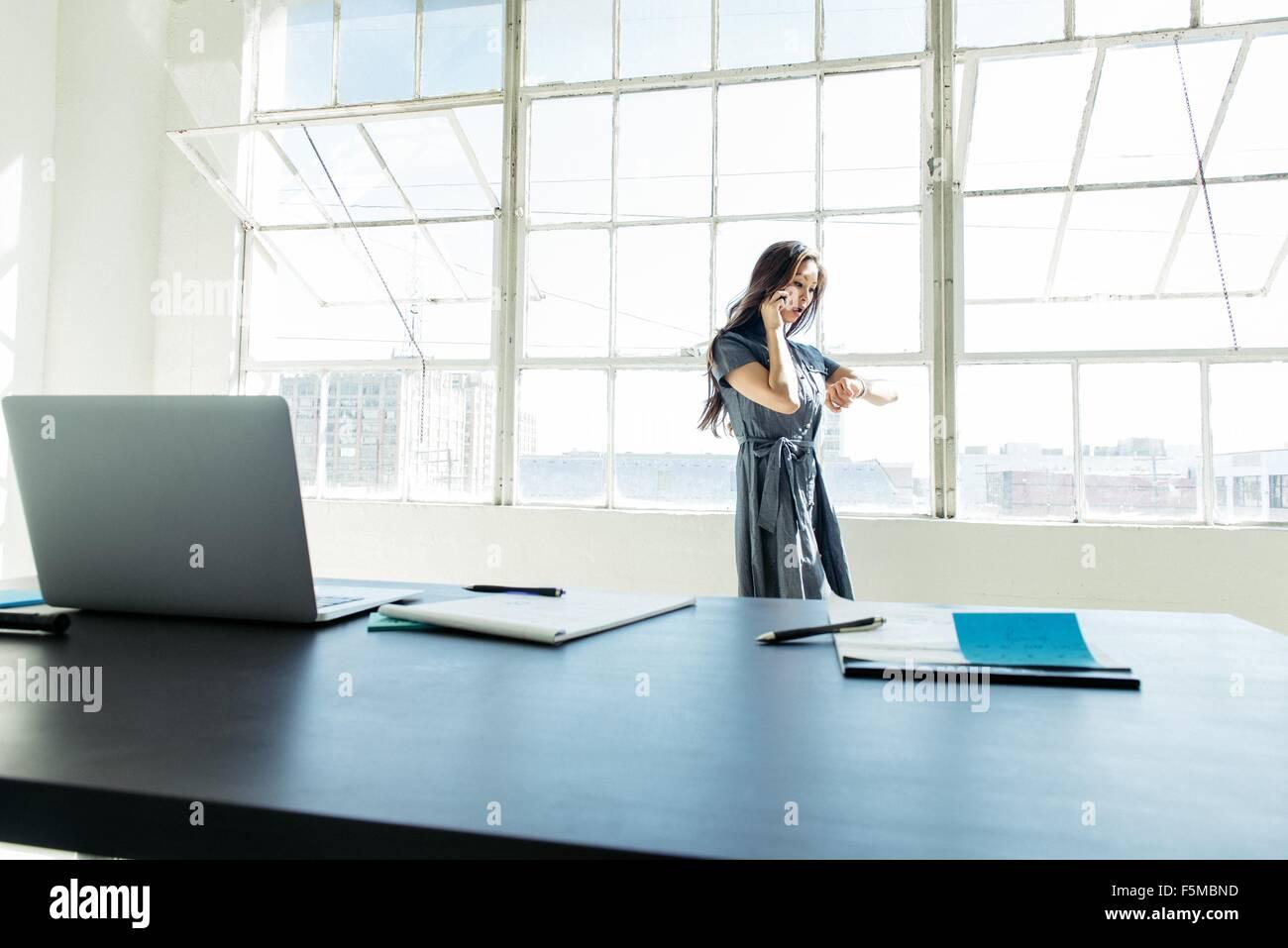 Imprenditrice parlando sullo smartphone dalla finestra di ufficio Immagini Stock