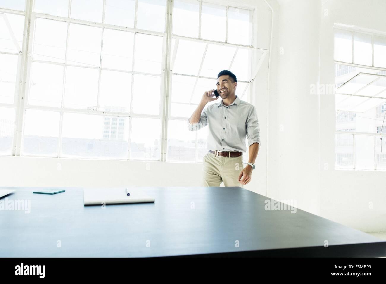 Imprenditore parlando sullo smartphone dalla finestra di ufficio Immagini Stock
