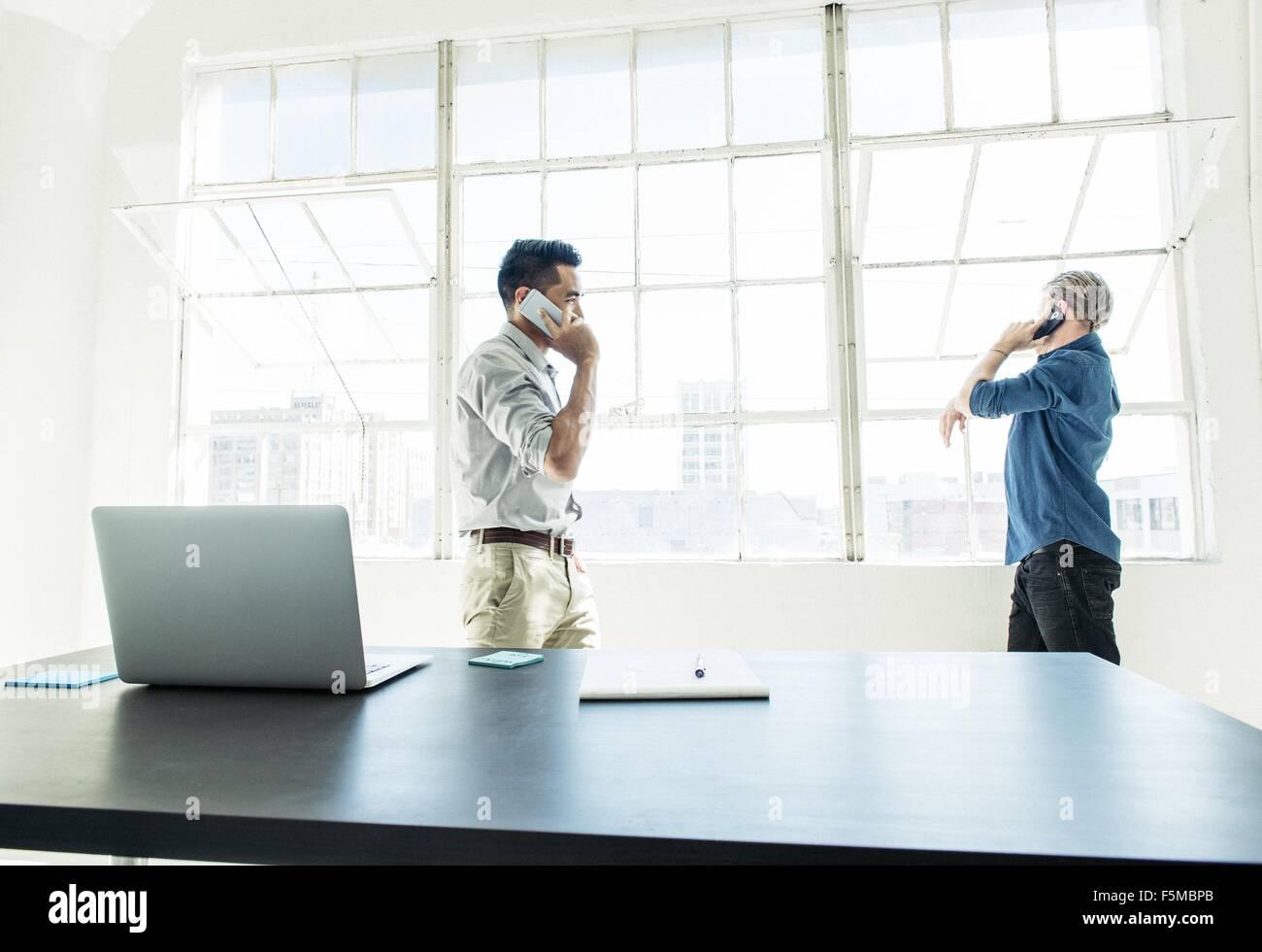 Imprenditori parlando sullo smartphone dalla finestra di ufficio Immagini Stock