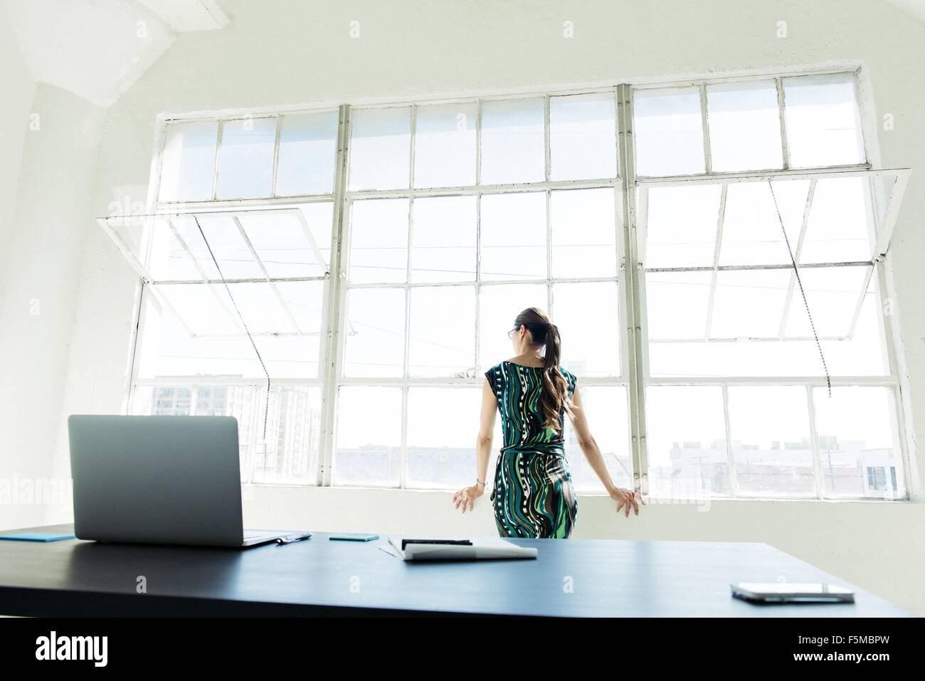 Imprenditrice guardando fuori della finestra di ufficio Immagini Stock