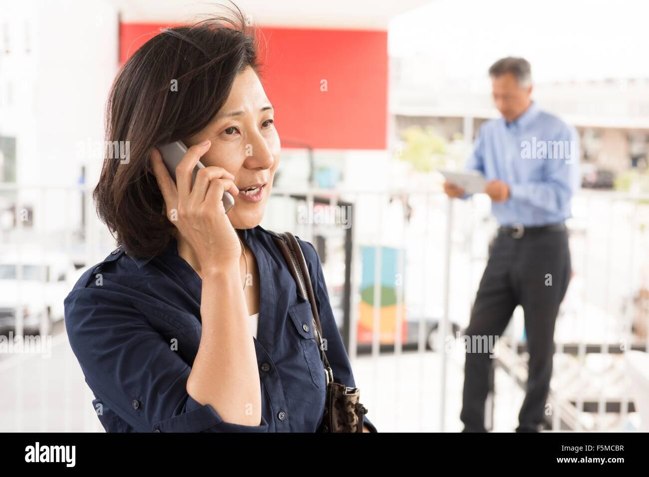 La testa e le spalle della donna matura parlando sullo smartphone che guarda lontano Immagini Stock