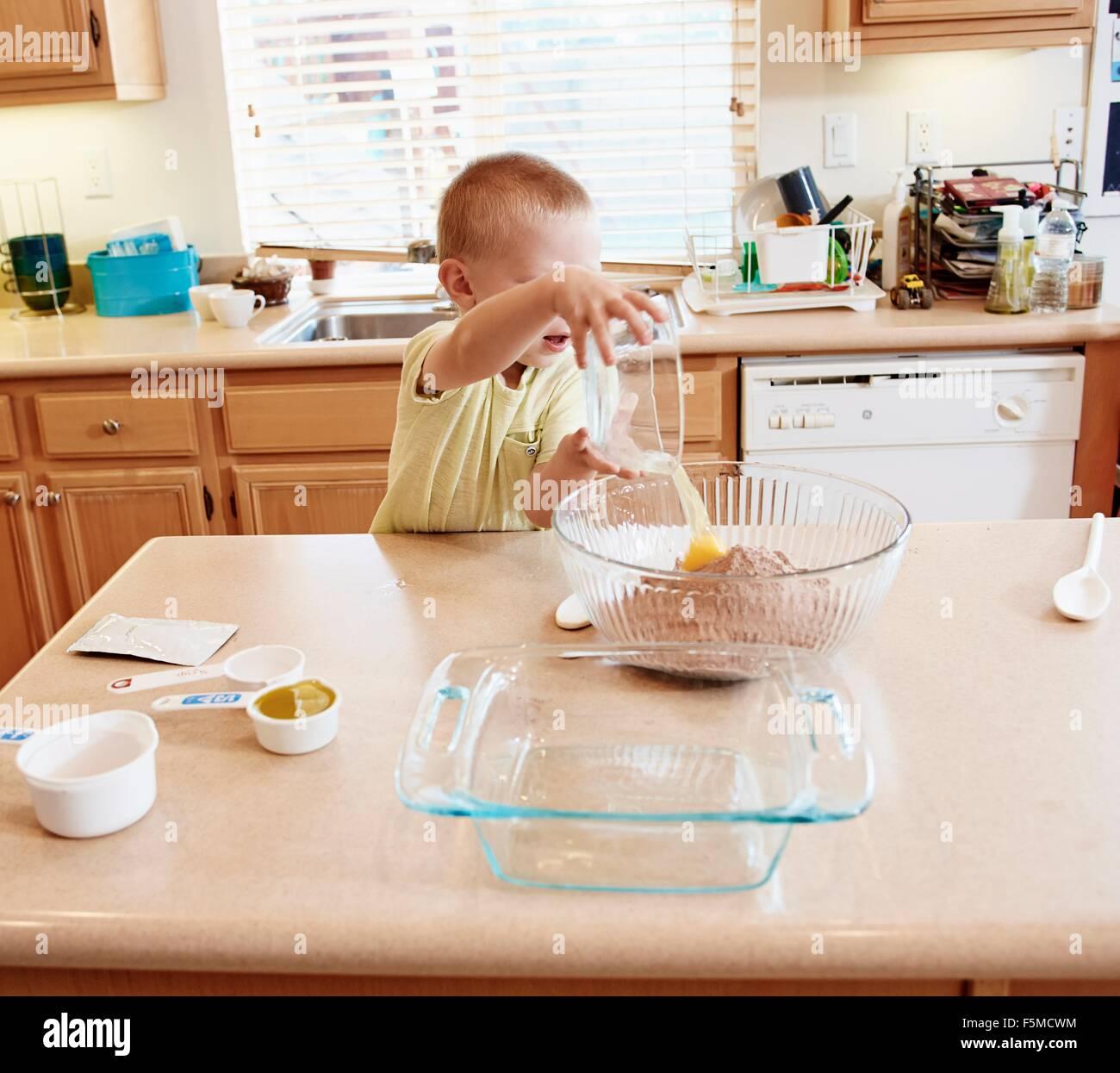 Ragazzo la preparazione della pastella nel recipiente di miscelazione Immagini Stock