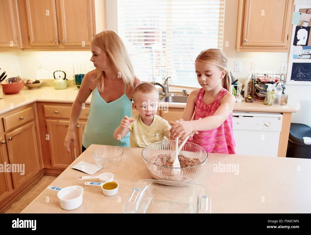 La famiglia la preparazione della pastella nel recipiente di miscelazione Immagini Stock