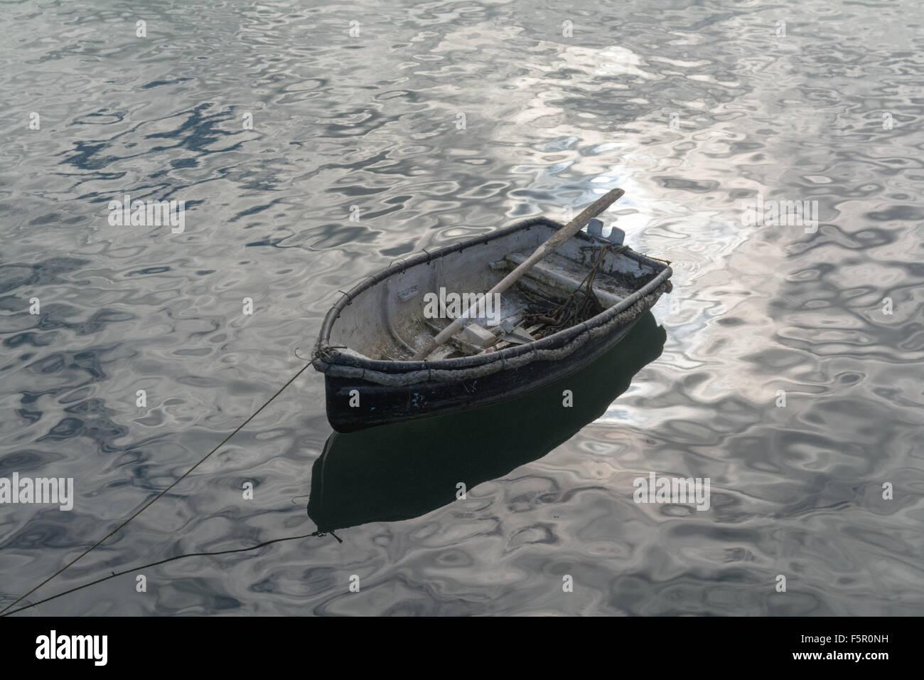 Piccola, vecchia barca a remi in un porto con una luce brillante riflesso da una superficie Immagini Stock