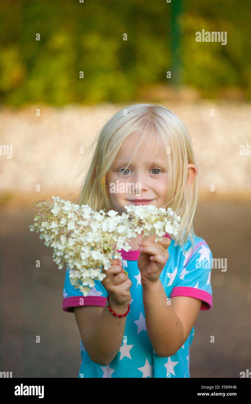 La Svezia, Sverige, Narke, Filipshyttan, Ritratto di una ragazza (4-5) tenendo i fiori Immagini Stock