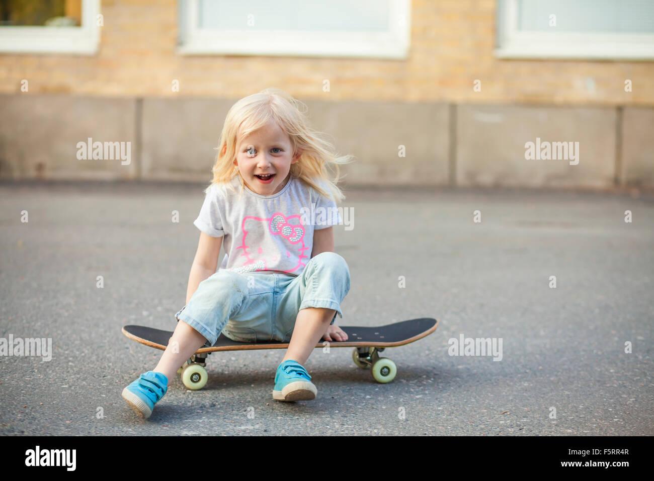 La Svezia, Vastergotland, Lerum, ragazza (6-7) seduto su skateboard Immagini Stock