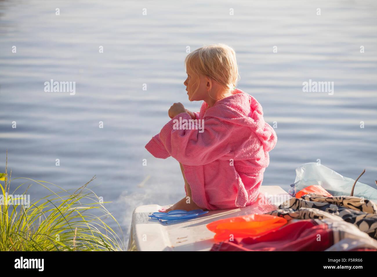La Svezia, Smaland, ragazza (6-7) seduto in accappatoio Immagini Stock