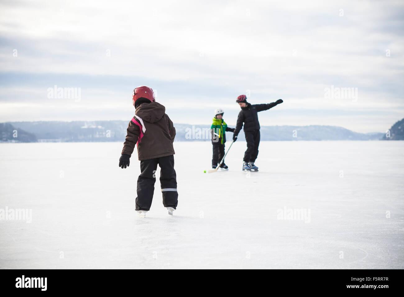 La Svezia, Vastergotland, Lerum, lago Aspen, Mom riproduzione di hockey su ghiaccio con i suoi due bambini (6-7, Immagini Stock