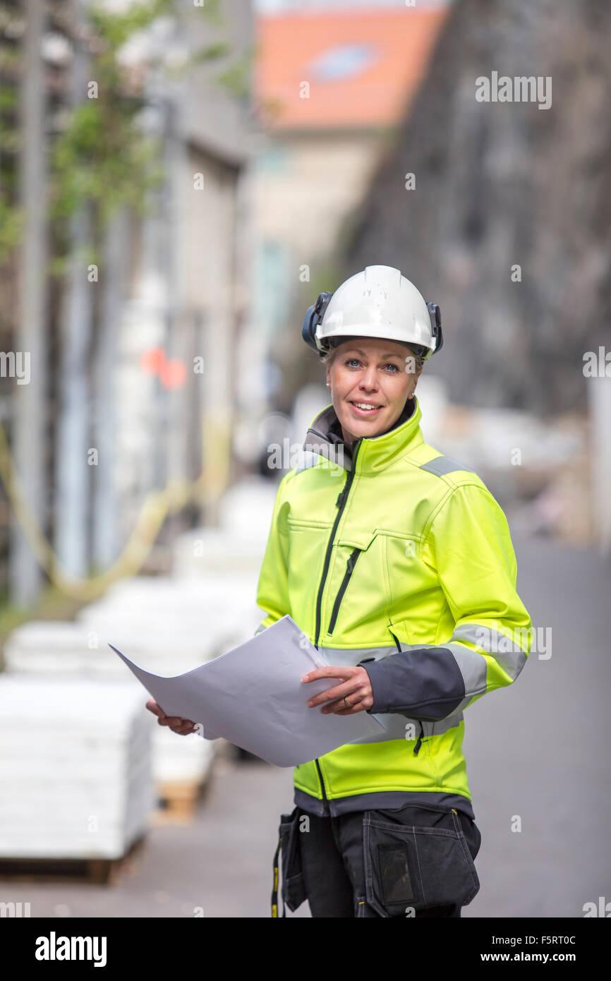 La Svezia, Vastergotland, Smiley lavoratore edile con blueprint Immagini Stock