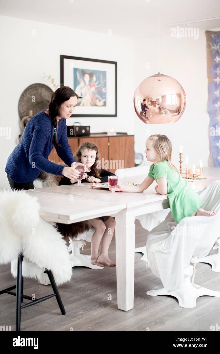 La Svezia, Mom dando succo di frutta per le sue figlie (6-7) Immagini Stock