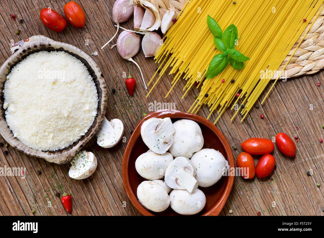 Alta angolazione di una tavola in legno rustico con gli ingredienti per preparare una ricetta di pasta, come ad Immagini Stock