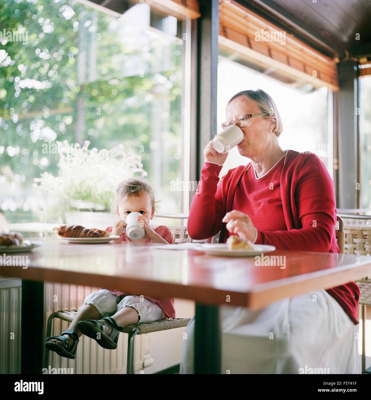 Finlandia, Helsinki, Uusimaa, la nonna e la nipote (2-3) rilassante in cafe Immagini Stock