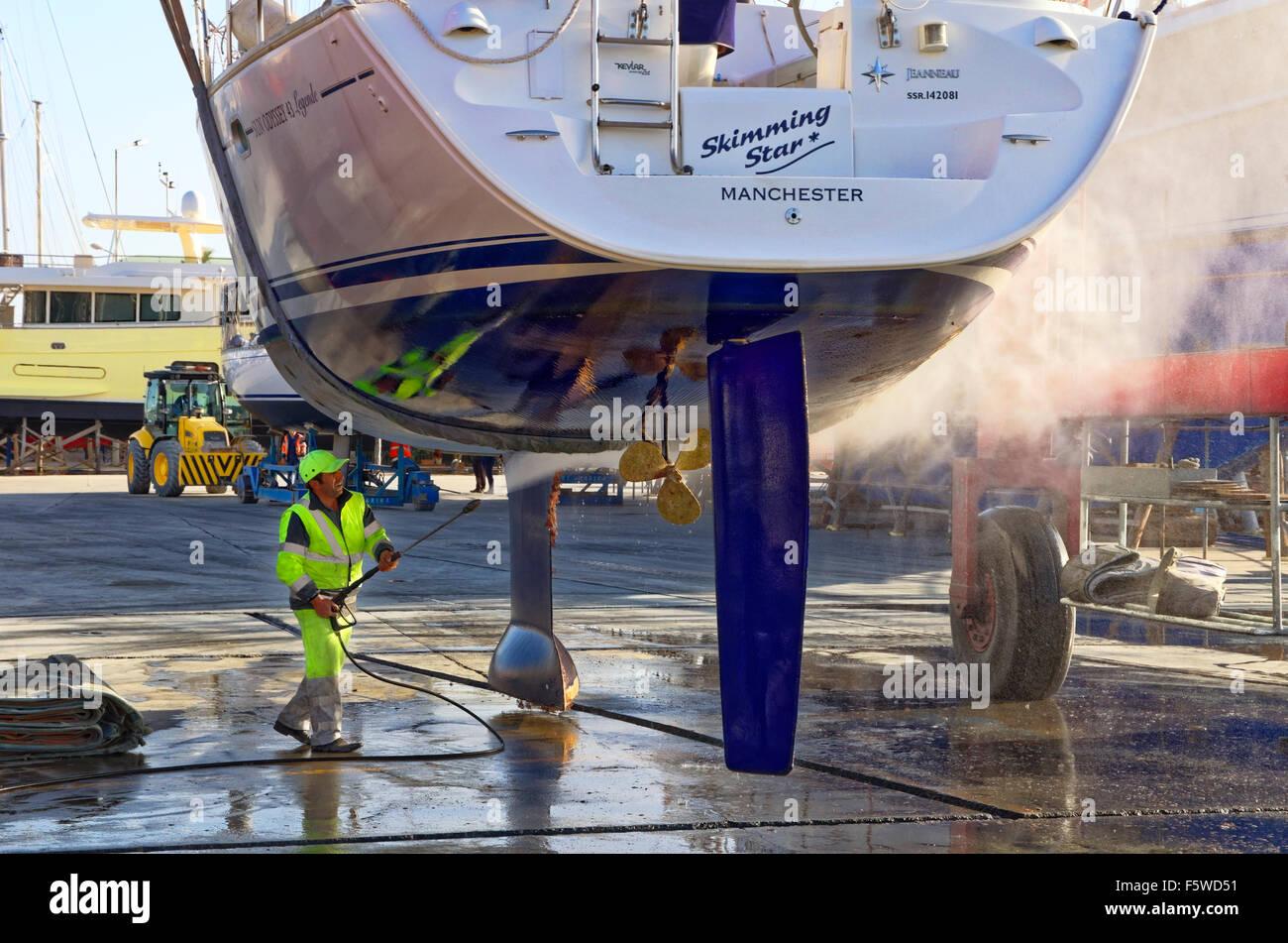 Yacht da crociera che viene sollevato e jet-lavata per rimuovere la incrostazione marina. Immagini Stock