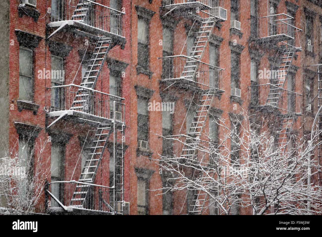 Facciata del Chelsea in mattoni con fuoco sfugge coperto di neve durante una nevicata invernale, Manhattan New York Immagini Stock