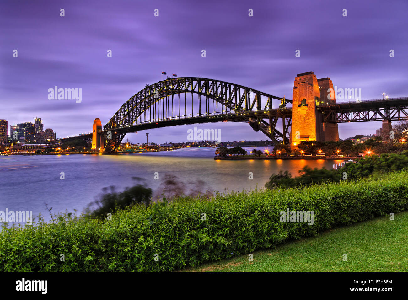 Vista laterale del famoso Ponte del Porto di Sydney al Tramonto con illuminazione dal verde parco ricreativo in Immagini Stock