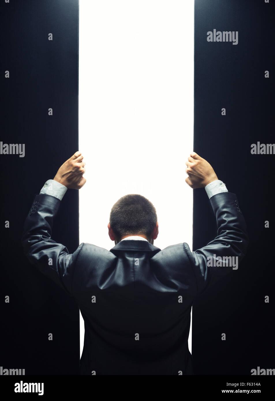 Imprenditore aprendo la porta a una luce brillante Immagini Stock