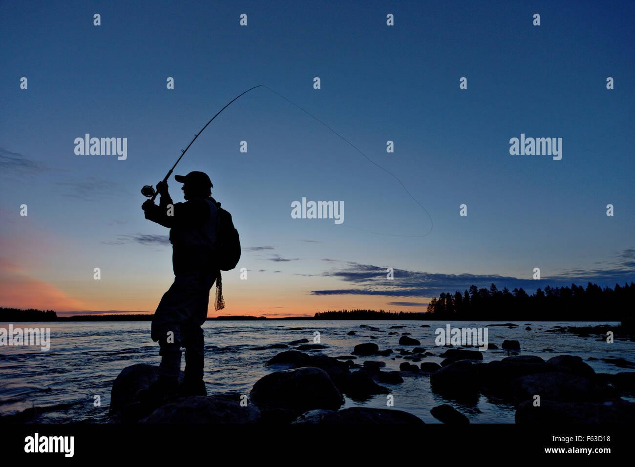 Fly fisherman cercando di catturare la trota fario. Lentua rapids, Kuhmo, in Finlandia. Immagini Stock