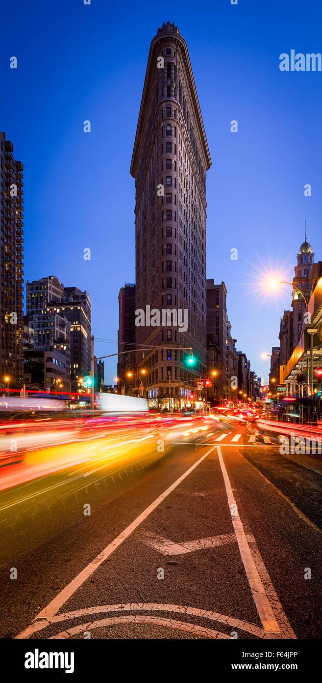 Flatiron Building con un cielo azzurro e auto sentieri di luce sulla Quinta Avenue al crepuscolo in Midtown Manhattan, Immagini Stock