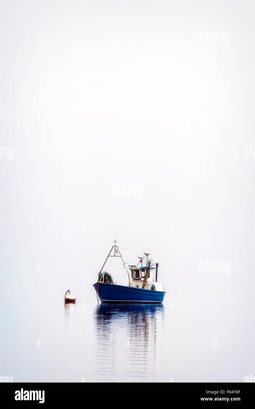 Una barca da pesca su un mare nebbioso Immagini Stock