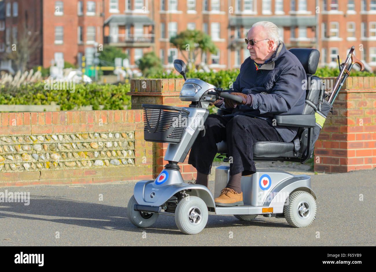 Mobilità scooter cavalcato da un uomo anziano in Inghilterra, Regno Unito. Immagini Stock