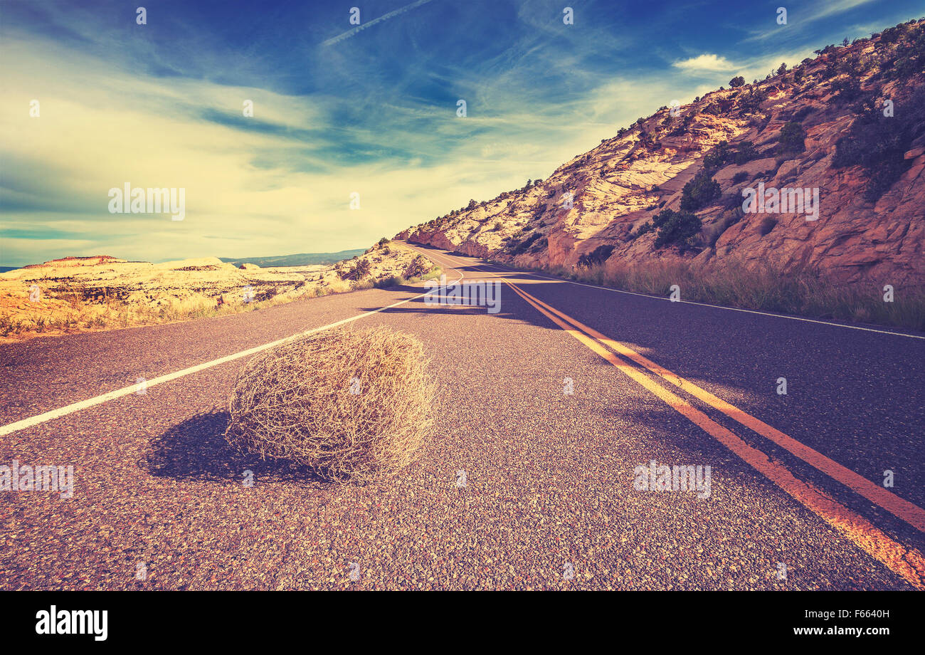 Vintage tonica tumbleweed sulla strada vuota, il concetto di viaggio foto. Immagini Stock