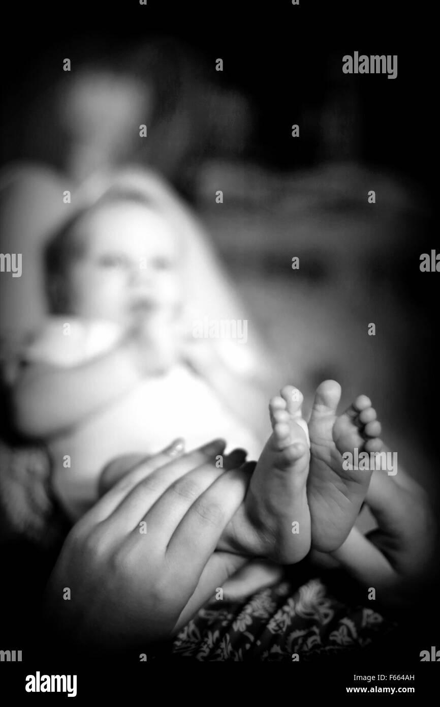 Madre tenendo le gambe del suo piccolo neonato e guardando il grazioso piccolo le dita dei piedi Immagini Stock