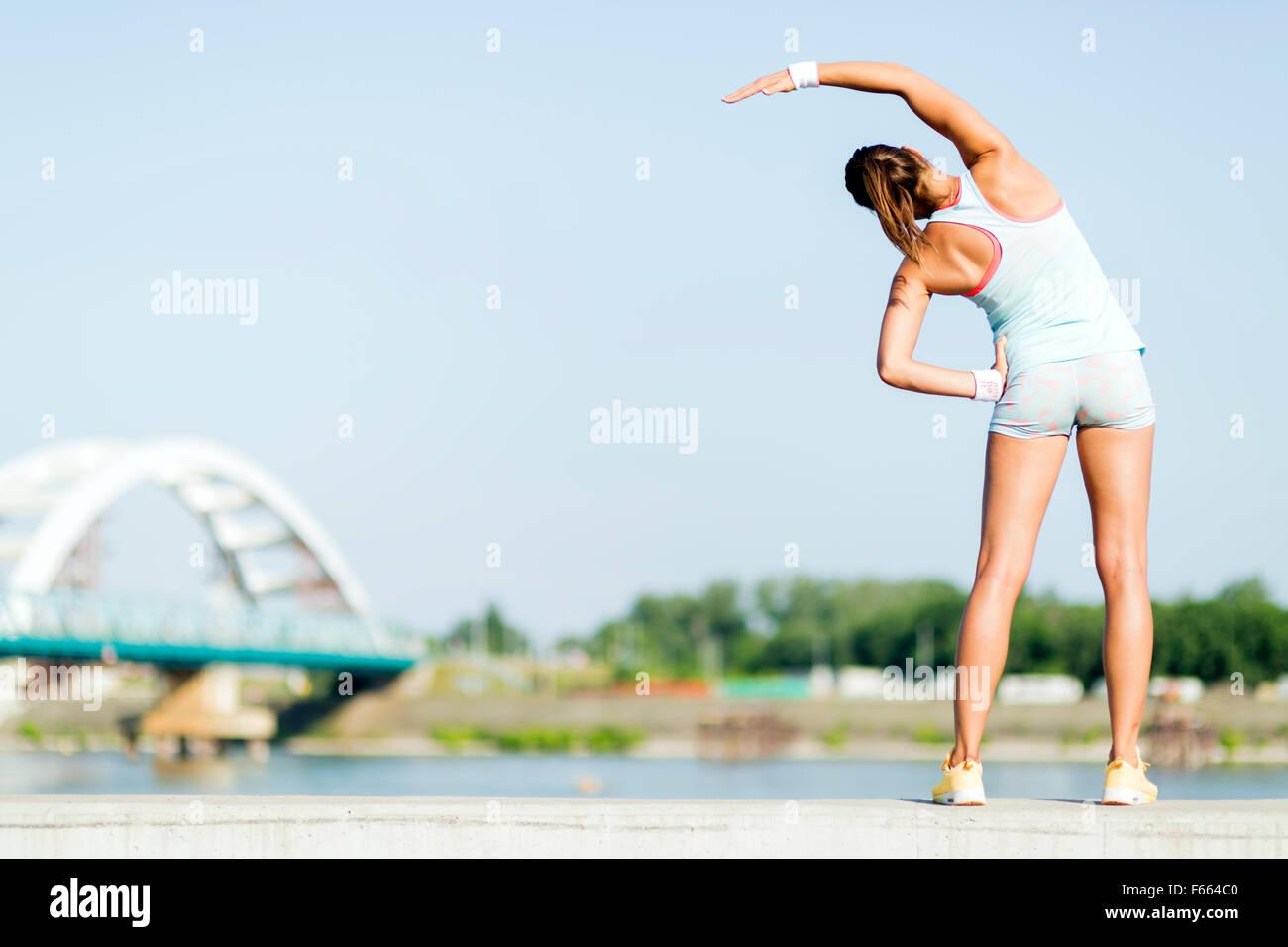 Giovane donna stretching e rilassante nella città prima di esercizio Immagini Stock