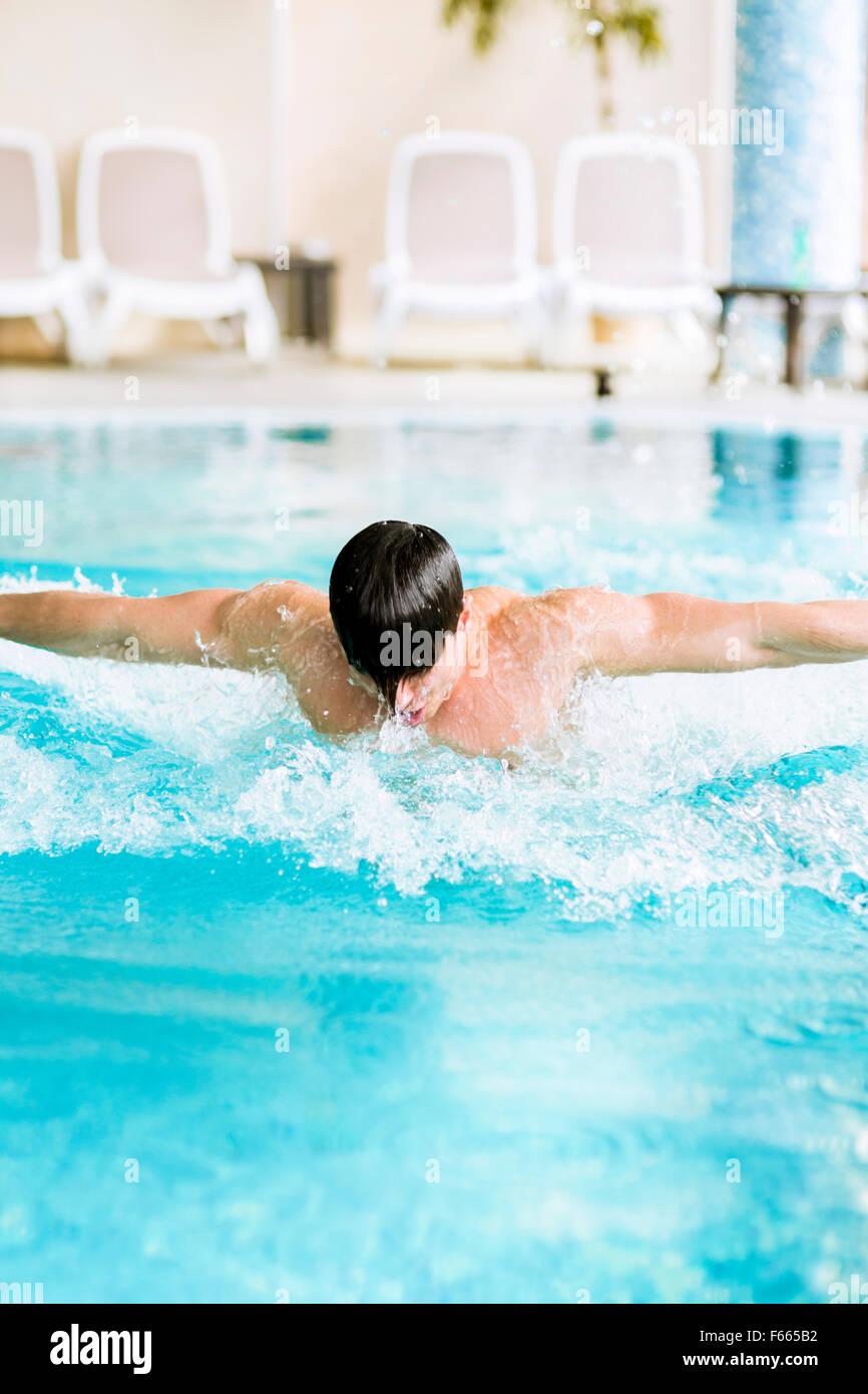 Corsa di nuoto di un bel muscolare di montare il maschio in un pool Immagini Stock