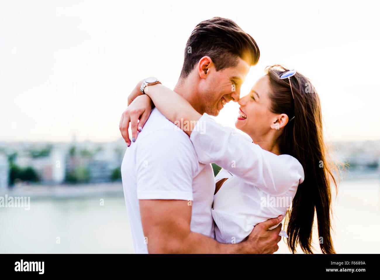 Giovane coppia romantica e abbraccia circa al bacio nel bel tramonto Immagini Stock