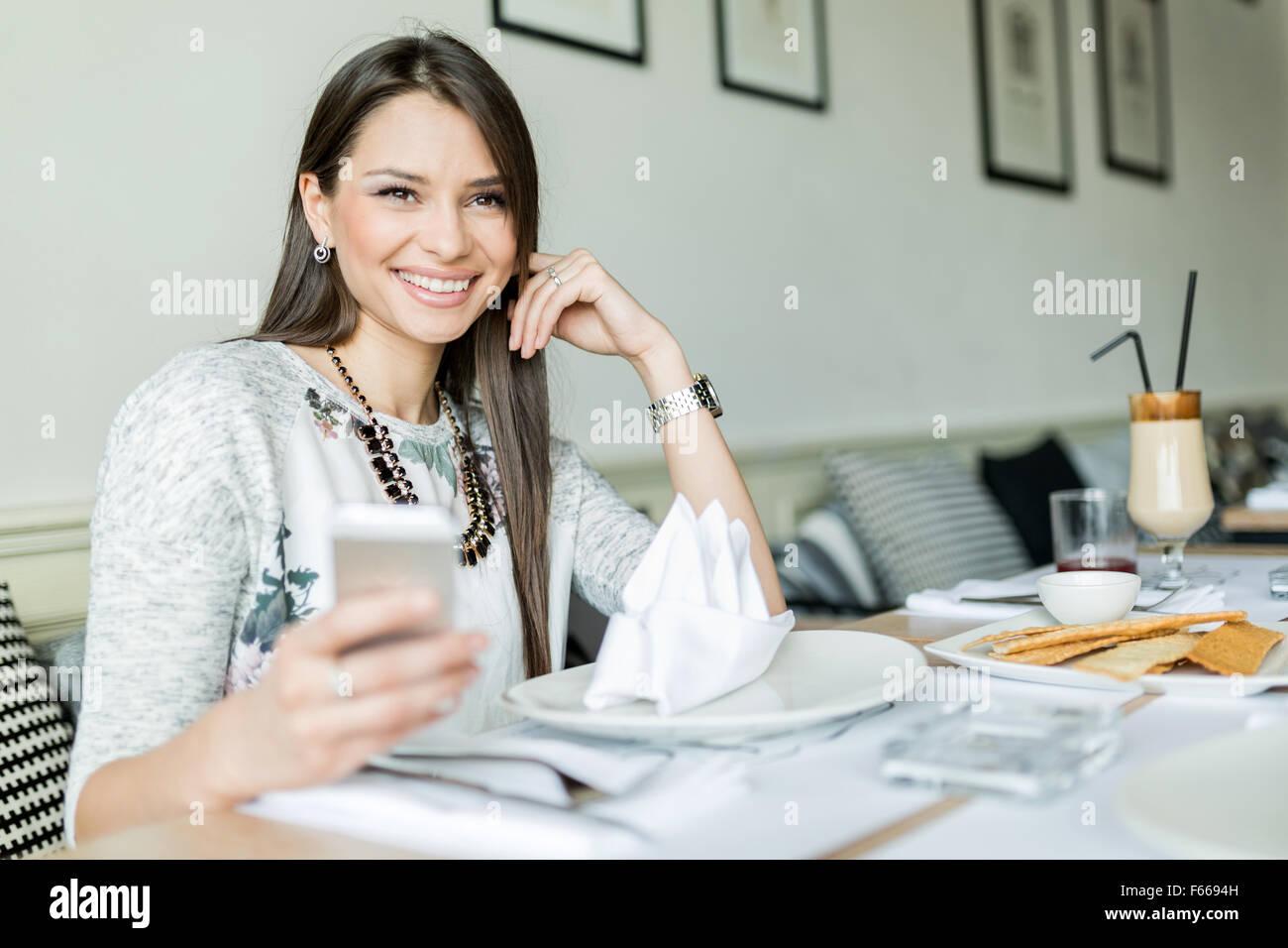 Bella signora sorridente seduto in un ristorante a un tavolo e tenendo premuto il suo telefono cellulare Immagini Stock