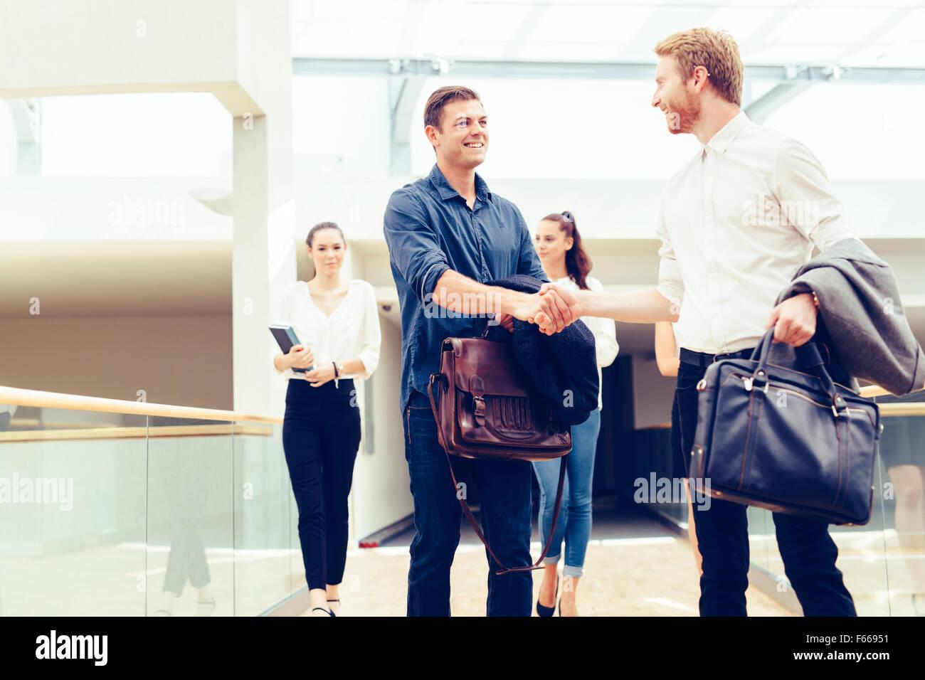 Uomini d'affari si stringono la mano e il messaggio di saluto ogni altro allegramente Immagini Stock