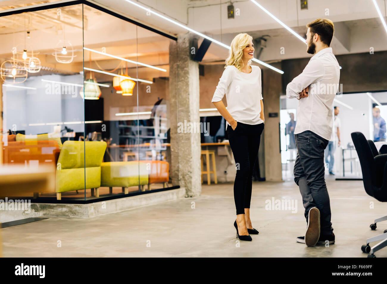 Due colleghi intelligenti che parlano in un ufficio moderno Immagini Stock