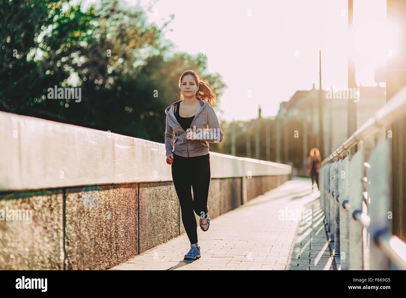 Montare donna jogging in città nel bel tramonto Immagini Stock