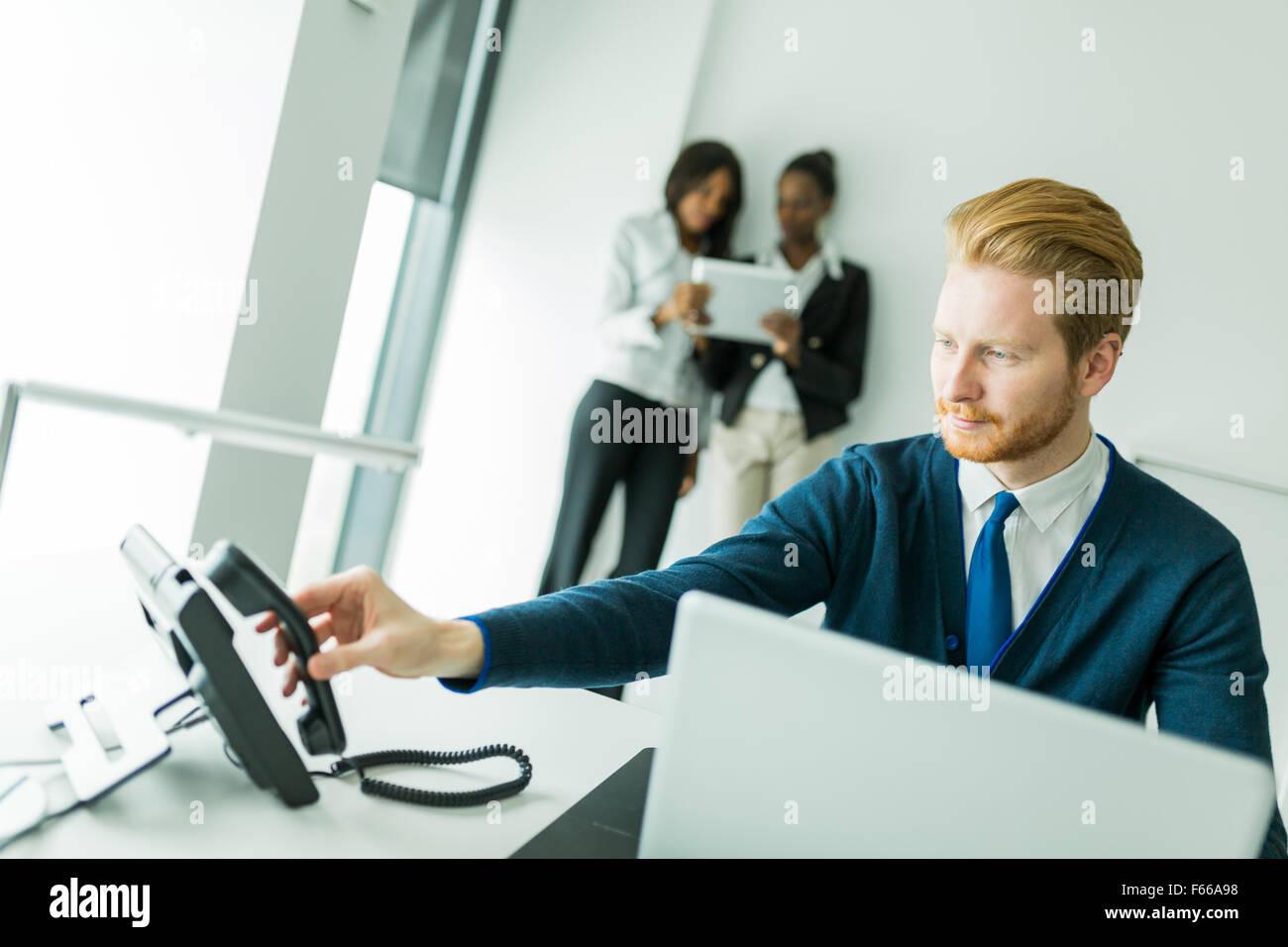 Imprenditore circa per rispondere al telefono con due belle, giovani donne avente una conversazione in background Immagini Stock