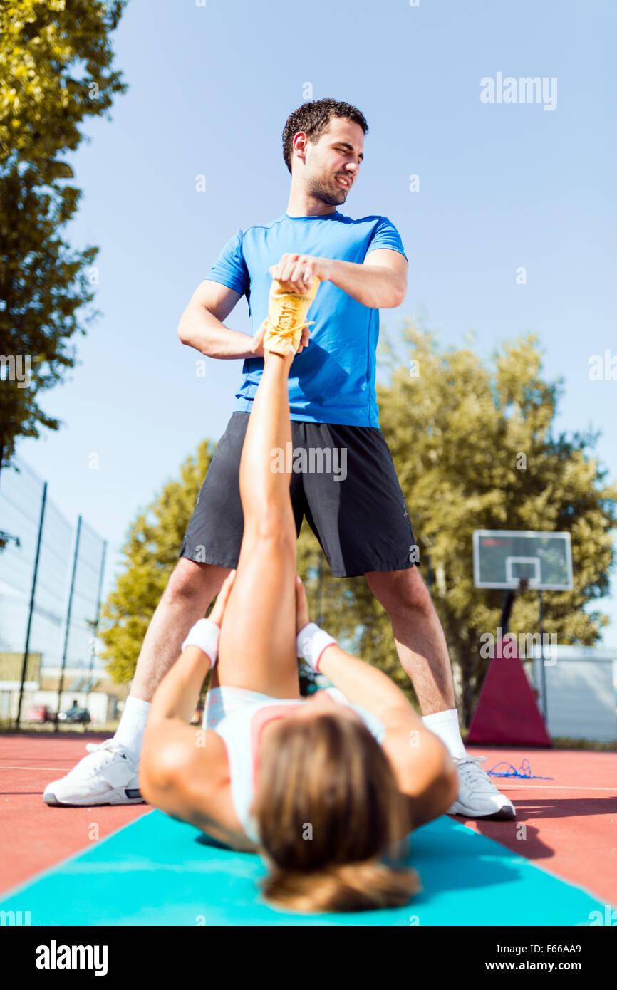 Giovani belle sportive aventi un ceppo e stirate dal trainer Foto Stock