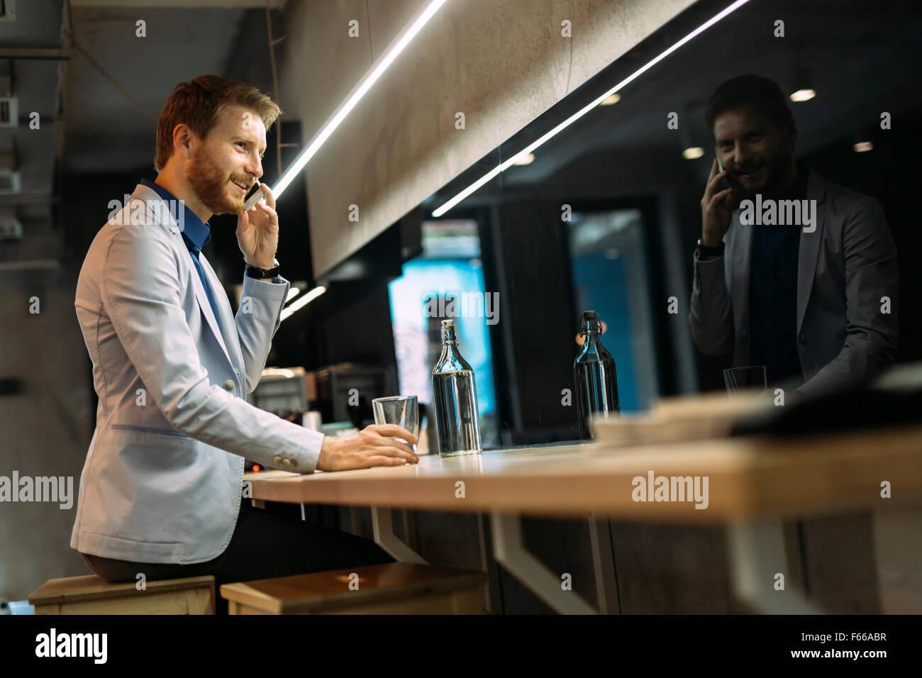 Occupato imprenditore parlando al telefono mentre è seduto in un pub Immagini Stock