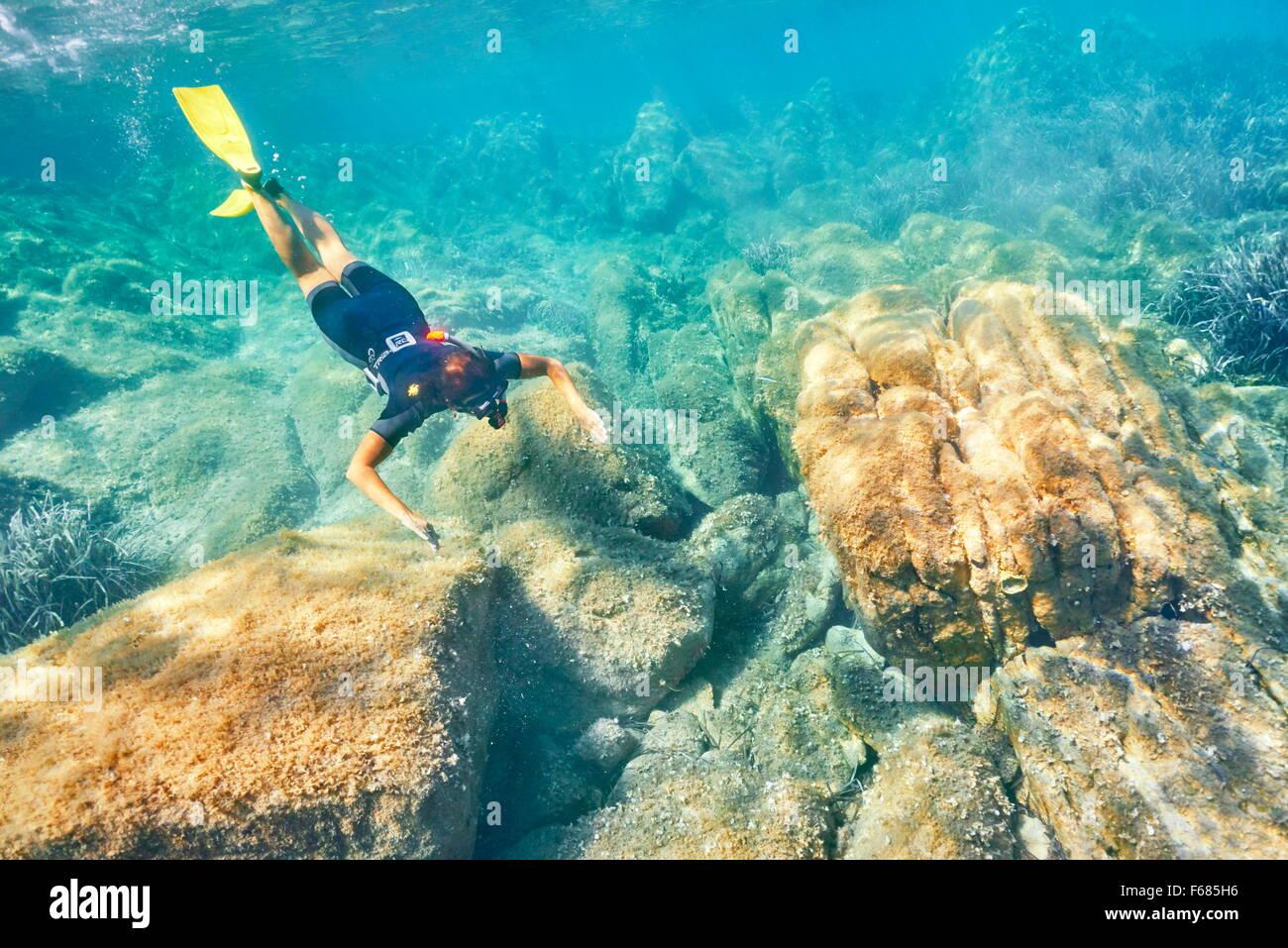 La donna lo snorkeling in acque turchesi, Punta dei Capriccioli, Costa Smeralda, Sardegna, Italia Immagini Stock